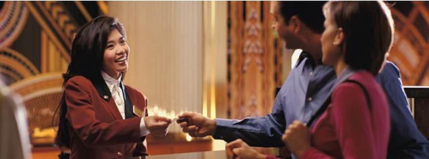 Receptionist greets hotel guests